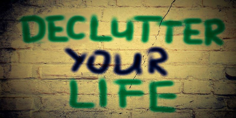 """Declutter - A picture of a brick wall with the words """"Declutter Your Life"""" spray painted on it."""