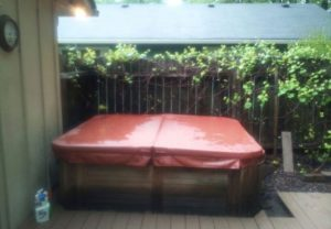 Hot Tub Removal - Picture of a old hot tub built into a wooden deck.