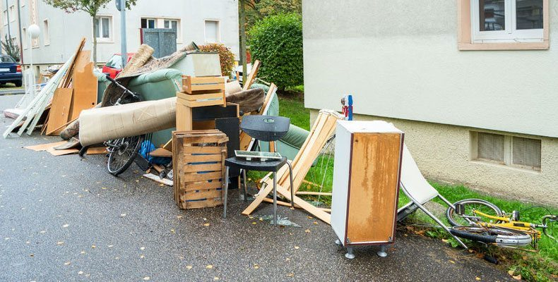 Curb Appeal - A picture of a big pile of junk and old broken furniture in from of a house.