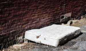 Mattress Removal - A photo of a old and dirty abandoned mattress on a backstreet.